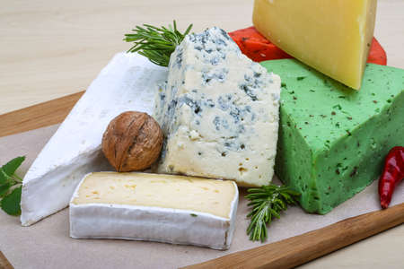 Assortment cheese with herbs on the wood background photo