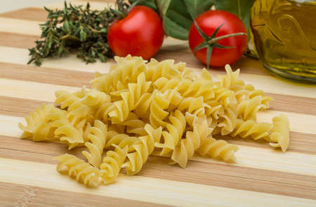 fusilli: Raw fusilli pasta on the wood background