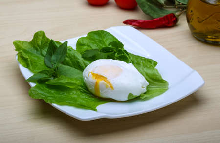 benedict: Egg benedict with salasd leaves on the wood background
