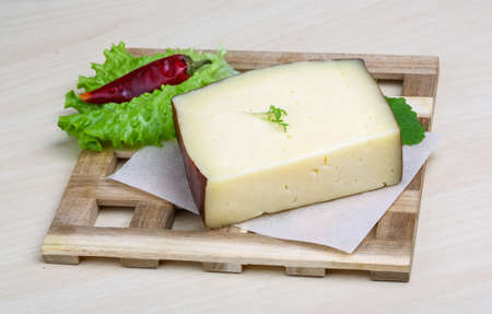 hard cheese: Hard cheese on the wood background with salad leaves