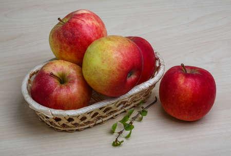 ambrosia: Poche mele nel cestino su legno backgrond Archivio Fotografico