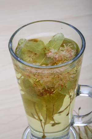 Linden tea in the glass on wood background photo