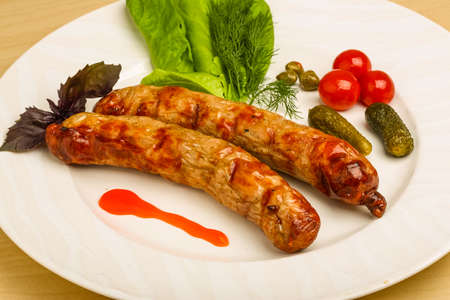 alcaparras: Grilled sausages served cucumbers, capers and salad leaves Foto de archivo