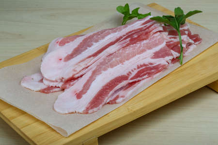 raw bacon: Raw bacon with green herb on the wood