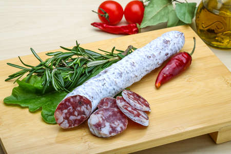 embutido: Spanish sausage - fuet salami with rosemary and salad Stock Photo