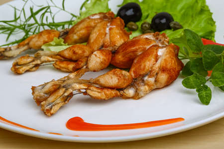 lunch tray: Fried frog legs with herbs on the wood background Stock Photo