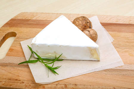 brie: Brie cheese with wallnut and terragon on wood background