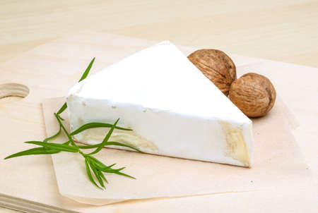 brie: Brie cheese with wallnuts and terragon on wood background Stock Photo