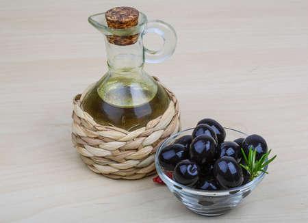 aceite oliva: El aceite de oliva con las bayas en el fondo de madera Foto de archivo