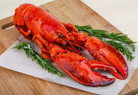 fish dinner: Fresh boiled lobster with rosemary on the wood background
