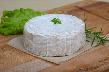 brie: Camembert brie cheese with herbs on the wood background