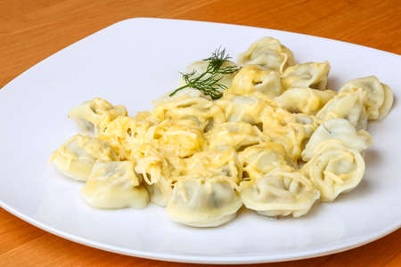 sause: Russian dumplings with cheese sause served dill branch Stock Photo