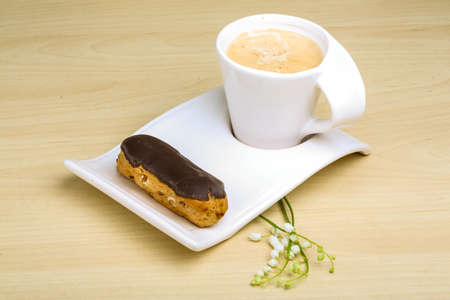 profiterole: Coffee with profiterole and the lily of the valley Stock Photo