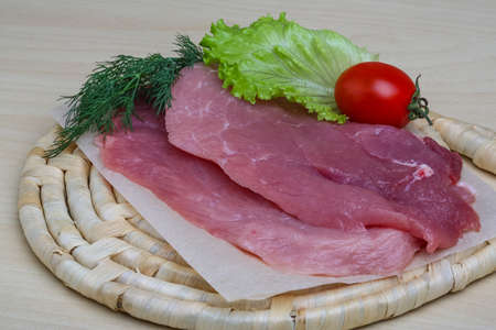 schnitzel: Raw pork schnitzel with dill - ready for cooking