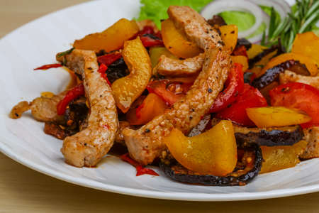 curry dish: Fried pork with vegetables - tomato, pepper, eggplant Stock Photo