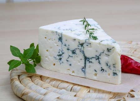 Blauwe kaas op de houten achtergrond met basilicum