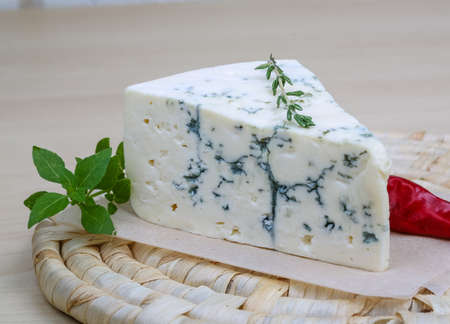 Blue cheese on the wood background with basil leaves
