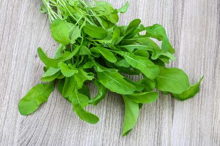 ruccola: Fresh green Ruccola leaves heap on the wood background