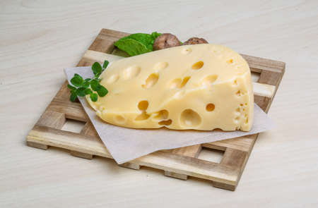 cheez: Yellow cheese with oregano leaves on the wood background