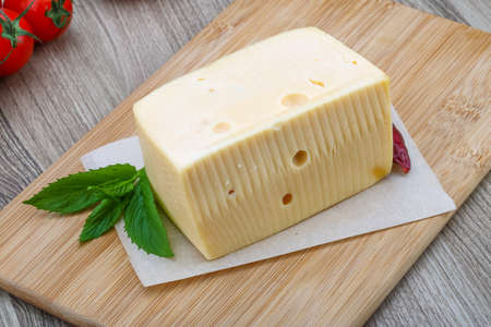 cheez: Yellow cheese brick with mint leaves on the wood background