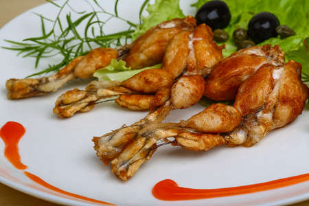 Fried frog legs with herbs on the wood background Standard-Bild