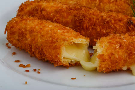 Fried cheese sticks in pan with dill Standard-Bild