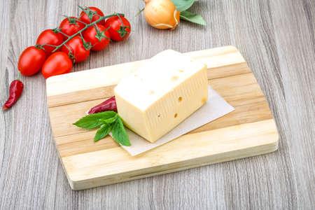 Amarillo ladrillo queso con hojas de menta en el fondo de madera