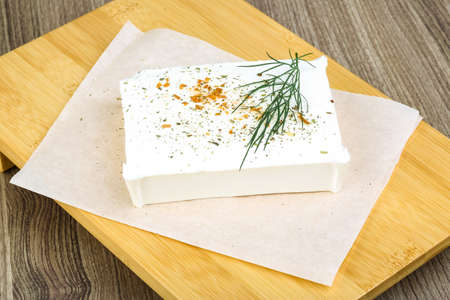 dill leaves: Feta cheese with dill leaves and spices on wood background Stock Photo
