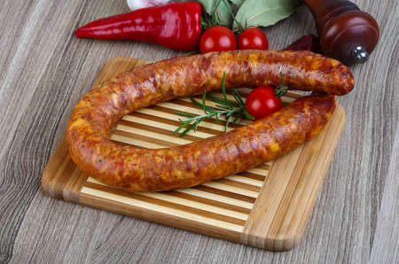 krakow sausage: Sausage ring with rosemary and pepper on the wood background