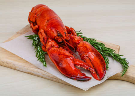 lobster dinner: Boiled lobster with rosemary on the wood background