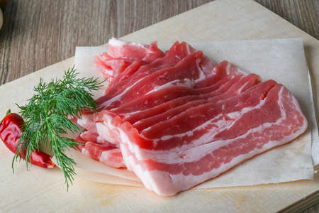 raw bacon: Raw bacon on the wood board with dill leaves Stock Photo