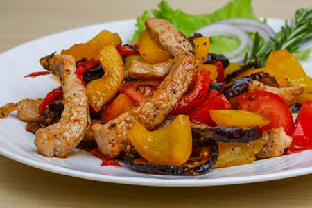 jamaican food: Fried pork with vegetables - tomato, pepper, eggplant Stock Photo
