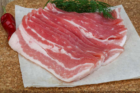 dill leaves: Raw bacon on the wood board with dill leaves Stock Photo