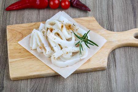 calamares: Anillos de calamar sin procesar con romero y especias - listo para cocinar Foto de archivo