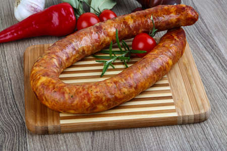 salami sausage: Sausage ring with rosemary and pepper on the wood background