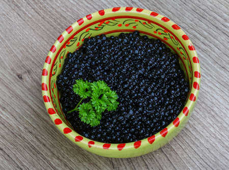 sturgeon: Luxury Black caviar in the bowl with parsley leaves Stock Photo