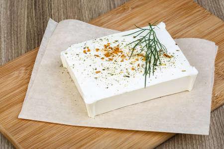 queso fresco blanco: Queso Feta con hojas de eneldo y especias sobre fondo de madera Foto de archivo