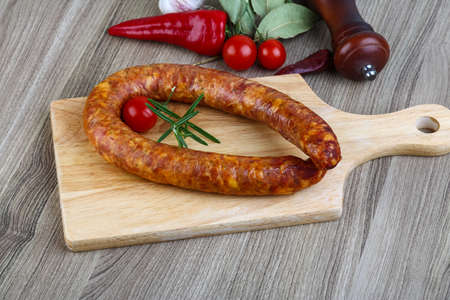Sausage ring with rosemary and pepper on the wood background