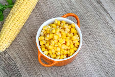 corn: Conservas de ma�z dulce en el taz�n de fuente en el fondo de madera
