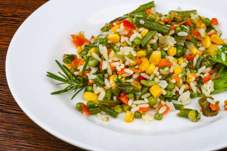 Mexican rice with vegetables and salad leaves Stock Photo