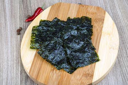 nori: Korean traditional snack - Nori seaweed sheets on the wood background Stock Photo