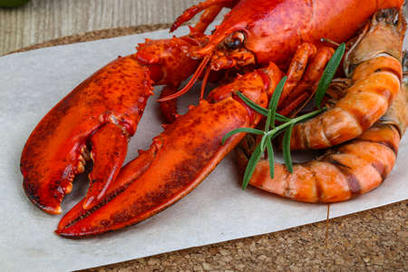 lobster dinner: Big cooked lobster and tiger shrimps ready for eating Stock Photo