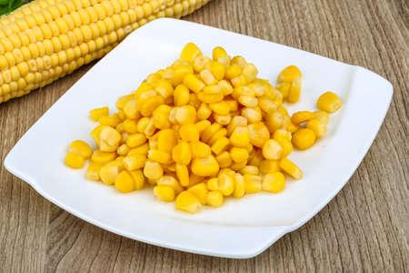 planta de maiz: Conservas de maíz dulce en el tazón de fuente en el fondo de madera