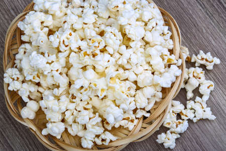 popcorn bowls: Fresh hot Popcorn in the basket on wood background