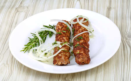 seekh: Hot Beef kebab with onion rings and rosemary Stock Photo