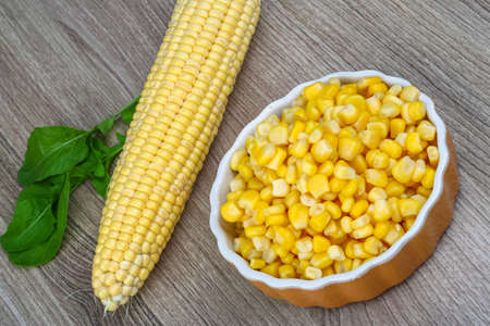 vegetable tin: Canned sweet corn in the bowl on wood background Stock Photo