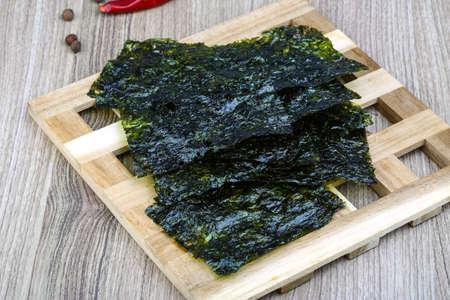 botanas: Merienda tradicional coreana - hojas de alga nori en el fondo de madera