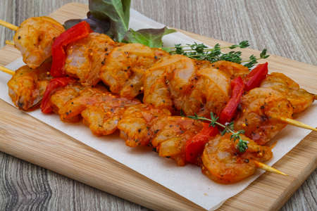 barbie: Raw tiger shrimps skewer with spices on the wood background