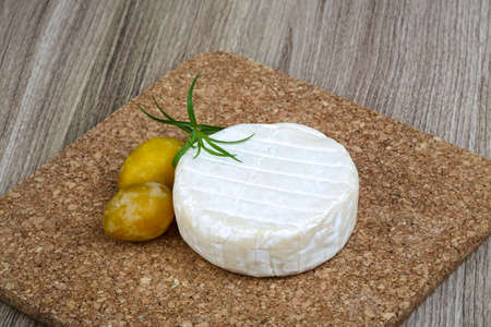 brie: Round Brie cheese with yellow plums and estragon