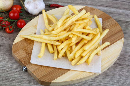 fast meal: French fries potato on the wood background Stock Photo